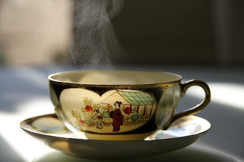 Gold-black-and-white ceramic teacup and saucer