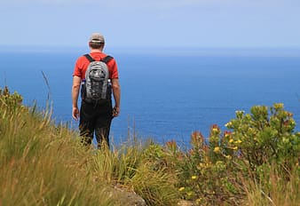 Man wearing backpack standing near cliff
