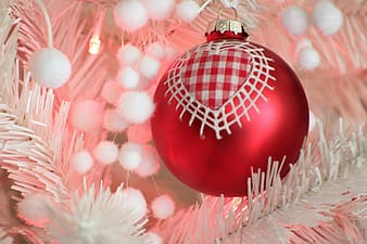 Red bauble on white christmas tree