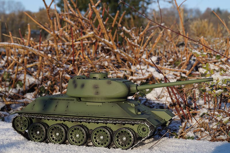 Green battle tank on brown dried leaves