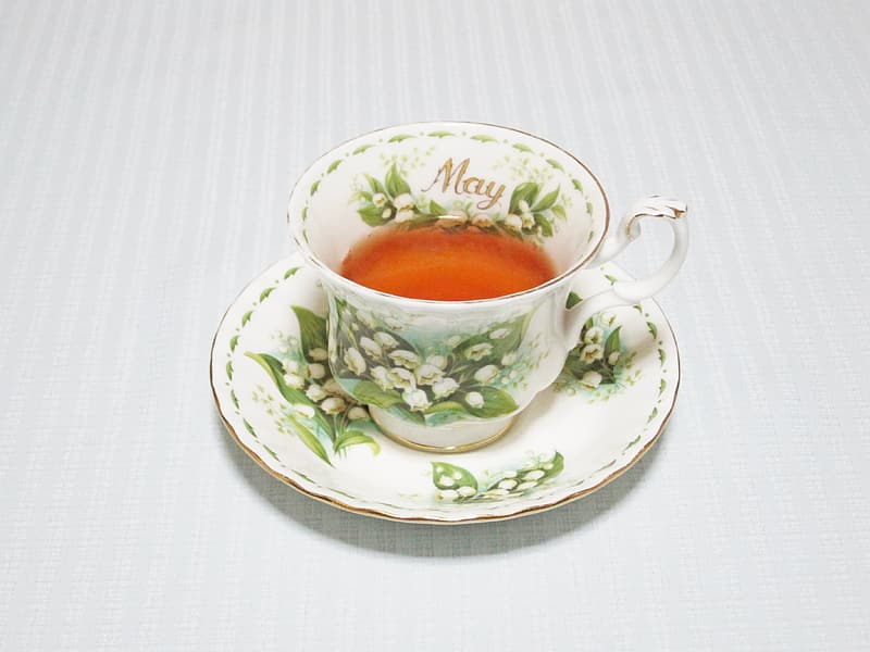 White and green floral teacup filled with brown liquid on saucer