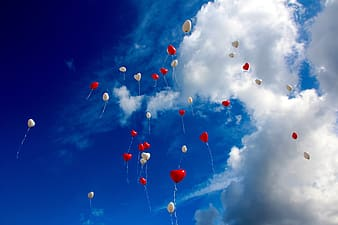 White and red heart balloons floating on sky