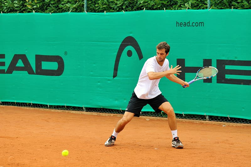 Tennis player wearing white shirt looking at the ball bouncing