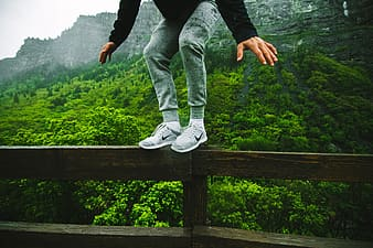 Man standing on rail and mountain at distance