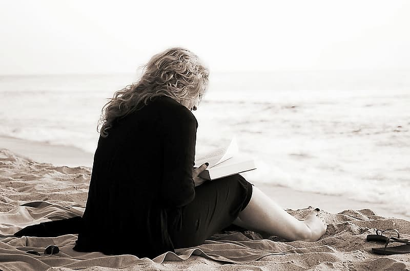 Woman sitting on sand reading book