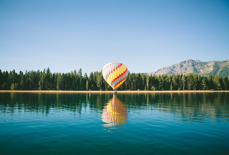 Hot air balloon floating over the lake