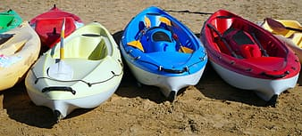 Blue red yellow and white boat on brown sand during daytime