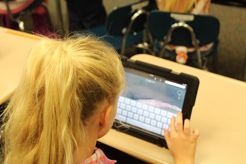 Blonde haired girl using black tablet computer