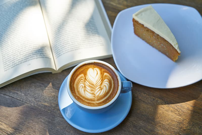 Latte with flower froth art beside plate with slice of cake
