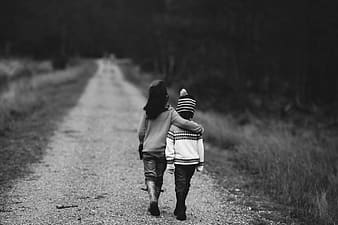 Two children walking grayscale photo