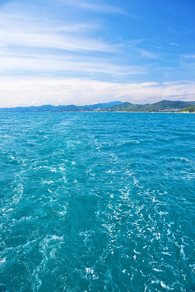 Green body of water under blue sky during daytime