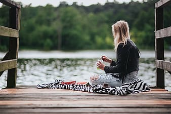 Woman in black jacket sitting on brown wooden dock during daytime