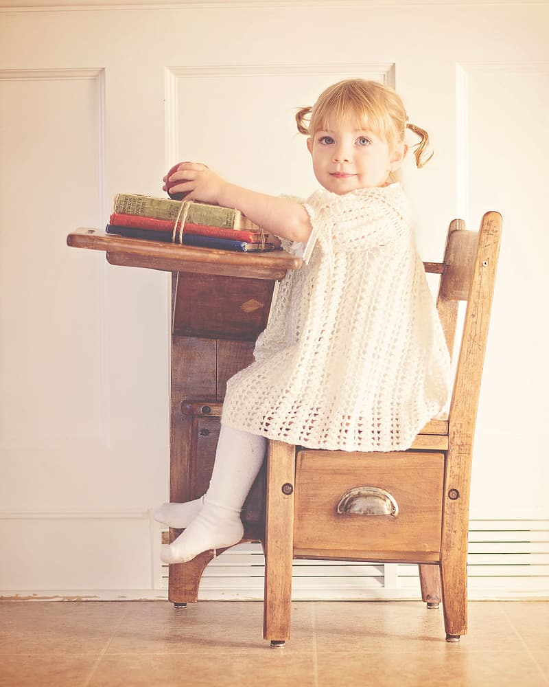 Girl in white knitted dress sitting on brown wooden school chair