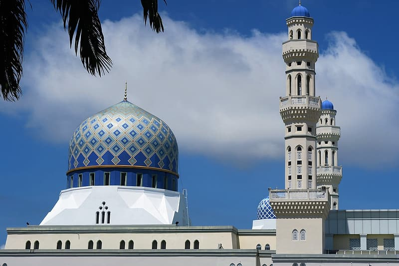 Blue and white mosque under cloudy sky at daytime