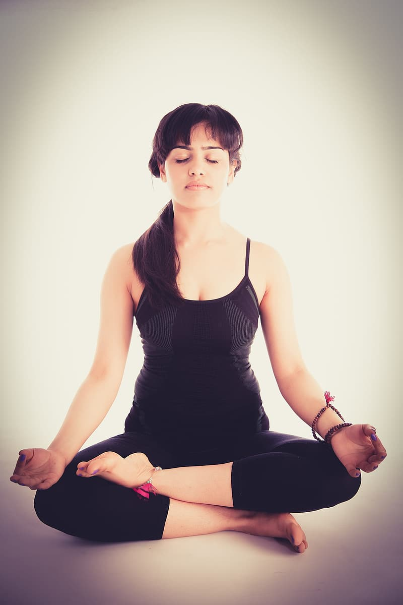 Woman in white camisole and leggins doing yoga