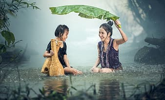 Two women playing under the rain