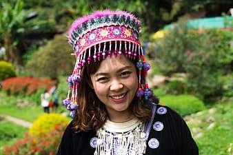 Smiling woman wearing black cardigan and multicolored headdress during daytime