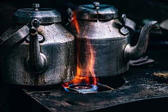 Two gray kettle sharing one burner stove