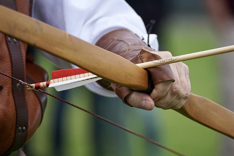 Person holding recurve bow with arrow
