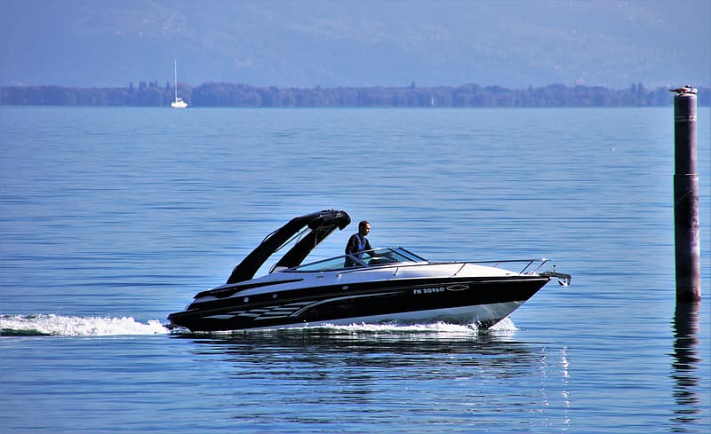 Black and white motor boat on sea during daytime