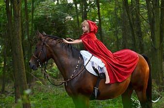 Woman in red robe riding brown horse