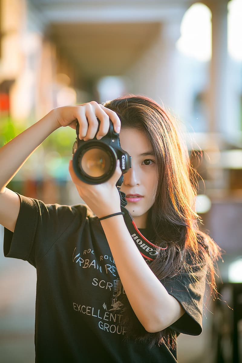 Woman wearing shirt while holding canon dslr camera