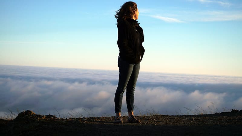 Woman standing on hill while while facing white clouds during daytime