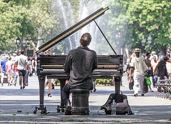 Back view of man playing grand piano in front of people