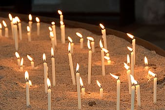 Lighted white candle sticks on white sand