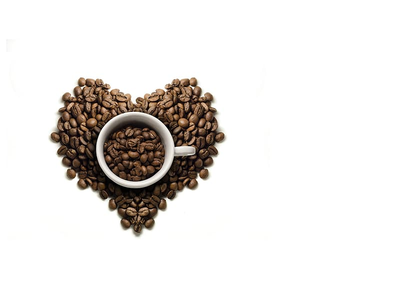 White ceramic coffee mug on coffee beans shaping at heart
