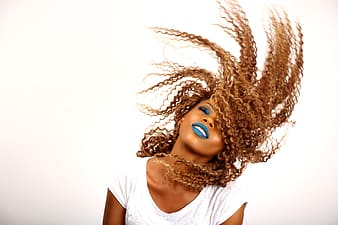 Woman with curly hair and blue lipstick closing her eyes