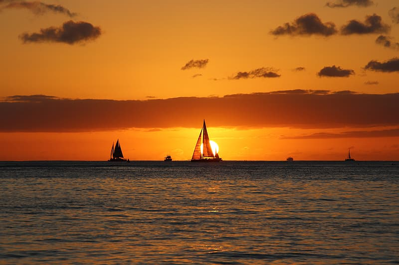 Silhouette of sail boat on sea during sunset