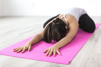 Woman in white t-shirt lying on purple yoga mat