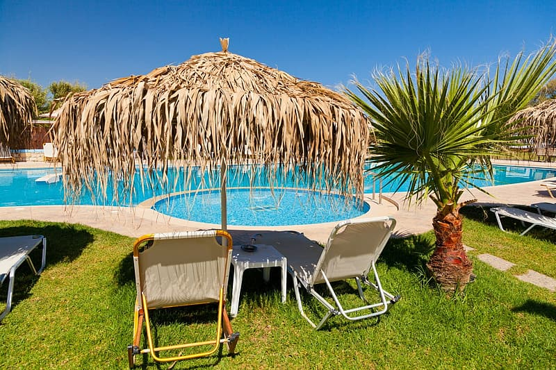 Brown wicker patio umbrella infront of pool