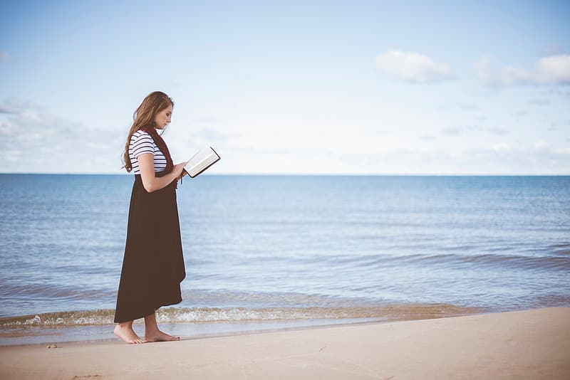 Woman reading a book while standing on beach sand during daytime