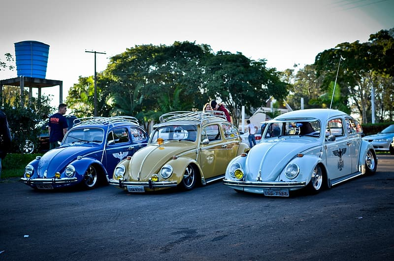 Three classic blue, brown and sky-blue Volkswagen Beetles during daytime