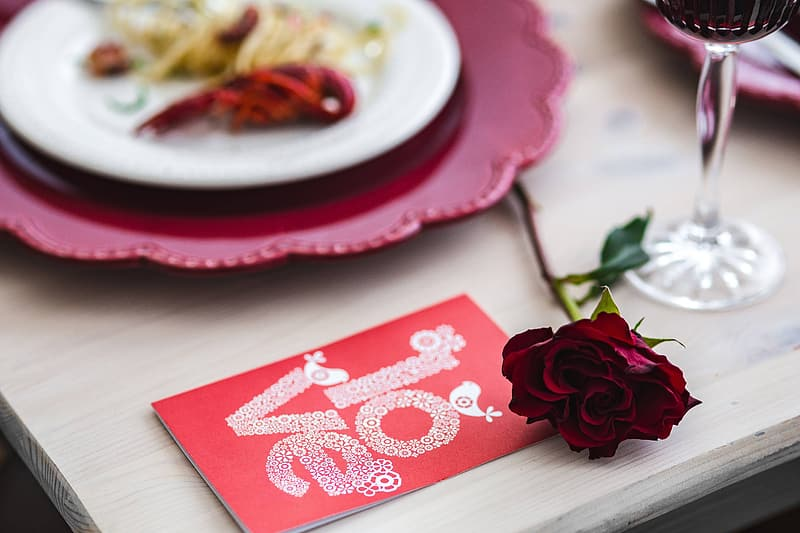 Red and white heart print card on white and red floral table cloth