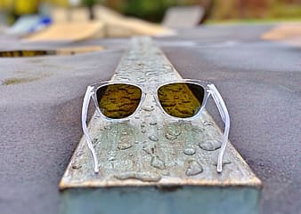 Clear plastic framed sunglasses on brown wooden board