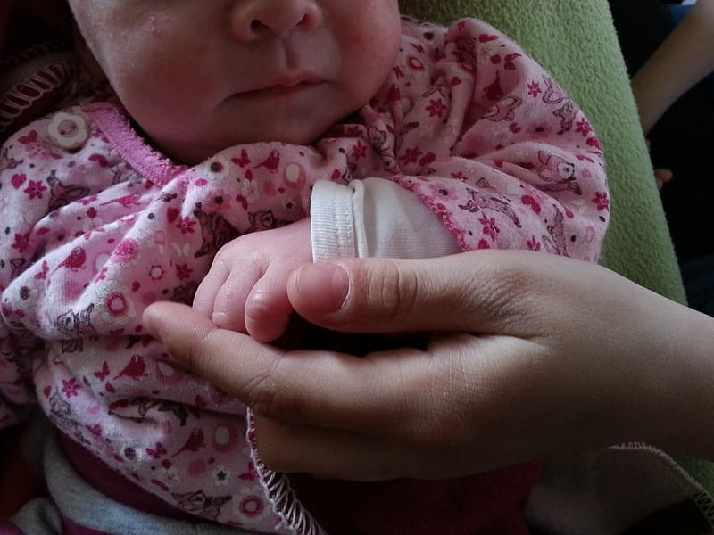 Baby holding person's hand