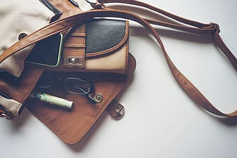 Brown leather sling bag beside black and silver camera