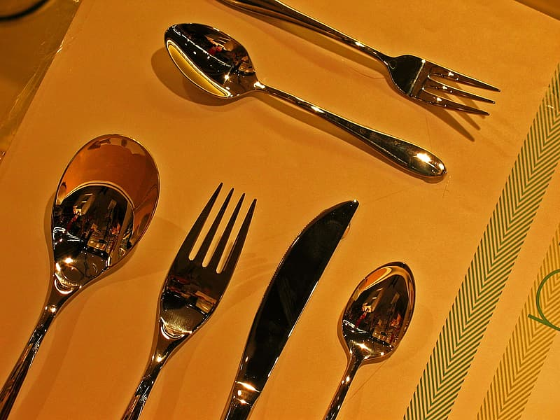 Silver fork and bread knife on yellow plate