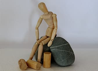 Human shaped wooden toy sits on black stones
