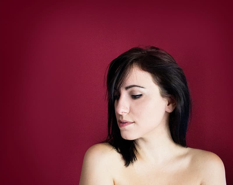 Topless woman with red background