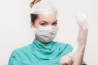 Woman wearing teal top and latex gloves