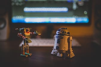 Star Wars R2-D2 toy figures on brown wooden table
