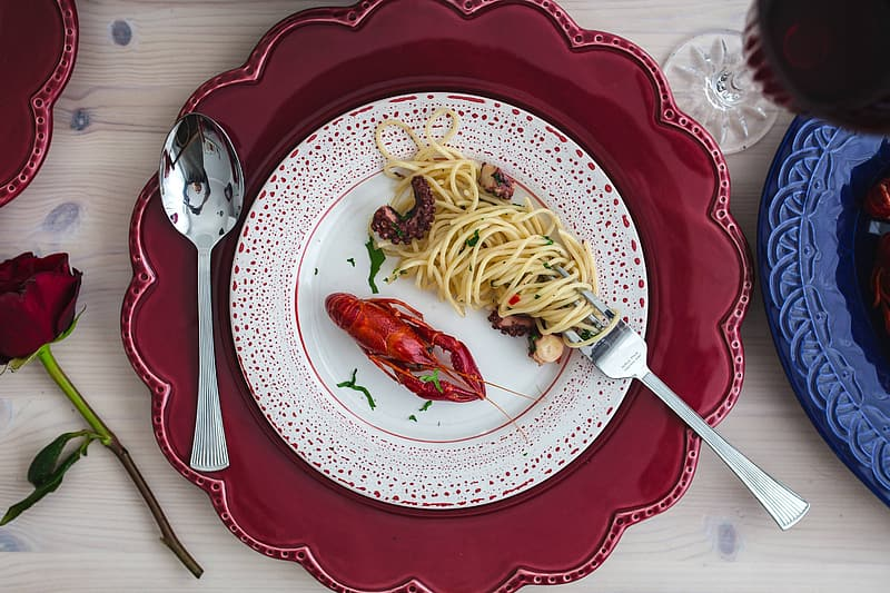 Pasta with red sauce on white and red ceramic plate