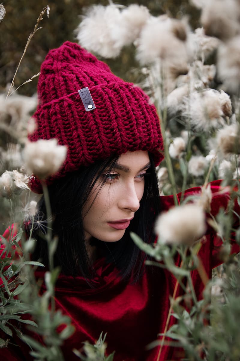 Closeup photo of woman wearing knit cap surrounded by dandelion flowers