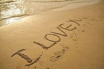 Brown sand with I LOVE YOU text during daytime
