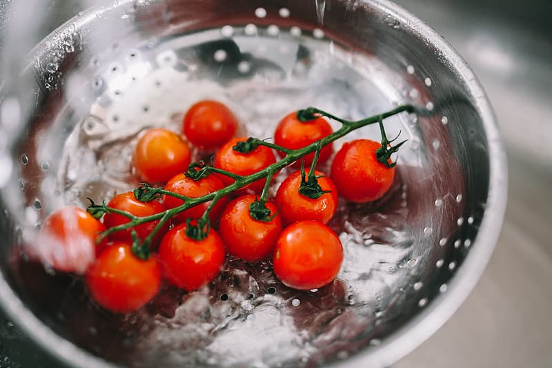 Red tomato on stainless steel bowl
