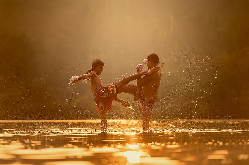 Two boy playing in water during golden hour